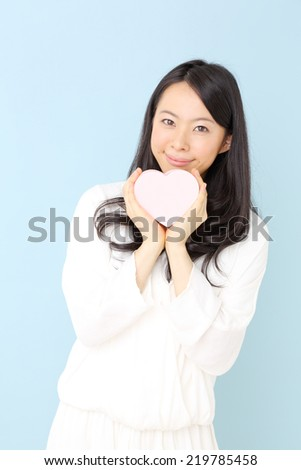 Cute young woman holding pink heart symbol against pale blue background