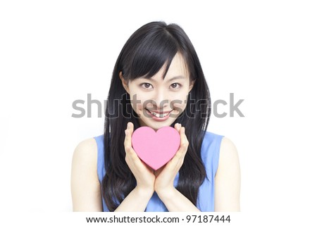 Cute young woman holding pink heart symbol, isolated on white background - stock photo