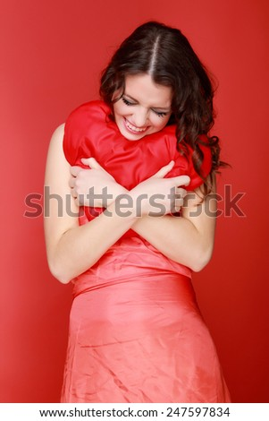 Cute young woman holds a heart symbol - stock photo
