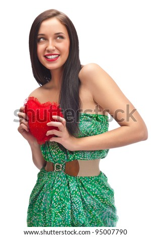 Cute young woman holds a heart symbol isolated on white background - stock photo