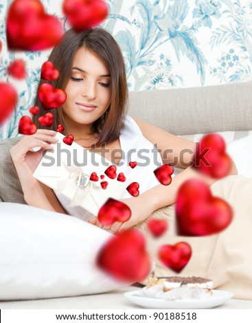 Cute young woman holds a valentine and reading it. Beautiful heart symbols flying around her. She is in love with her couple - stock photo