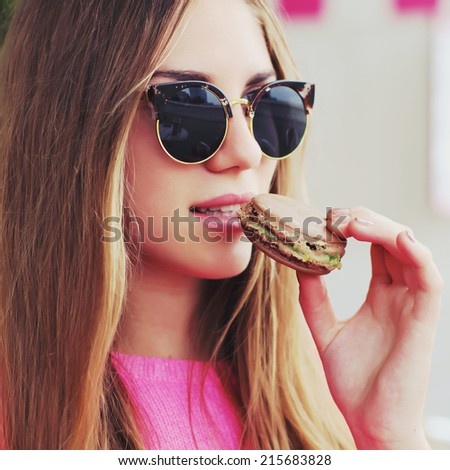 Cute young woman in a cafe eating macaroon. Photo toned style Instagram filters - stock photo