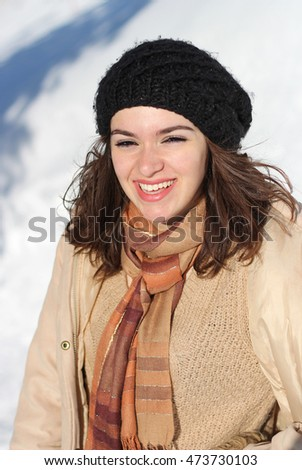 Cute young woman in beige jacket and black winter hat posing in the snow on a sunny winter day in the mountain. Winter portrait of Caucasian girl.