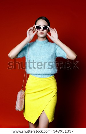 Cute young woman  in glasses wearing blue and yellow cloth on red background