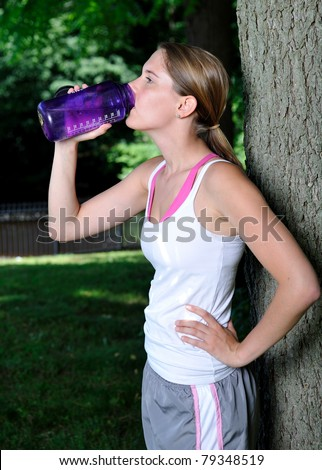 Cute young woman in white tank-top taking a break from her exercise routine outdoors by leaning against a tree and taking a drink of water from a reusable container - stock photo