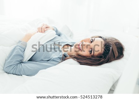 Cute young woman lying in bed in the morning and smiling