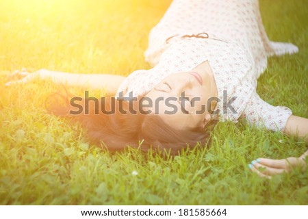 Cute young woman lying on the grass in the sunshine. Soft focus with shallow depth of field.  - stock photo