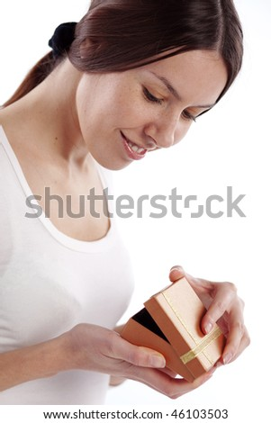 Cute young woman opening gift box close-up