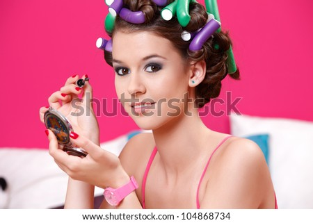cute young woman painting her eyes - stock photo