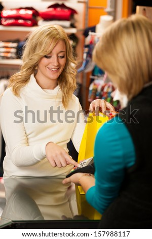 Cute young woman paying after successful purchase with credit card - girl in shopping