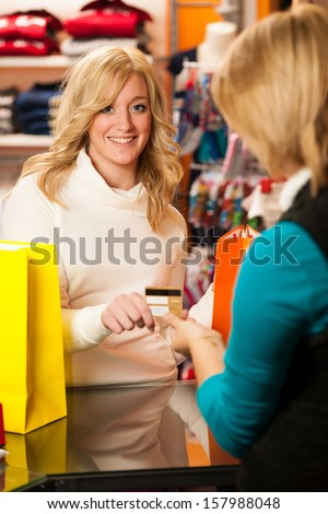 Cute young woman paying after successful purchase with credit card - girl shopping in clothes shop - stock photo