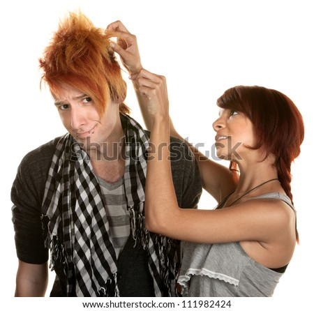 Cute young woman picking at her friends hair - stock photo