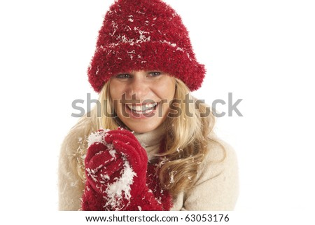 Cute young woman playing with snow in winter clothes