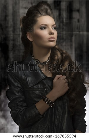 cute young woman posing in fashion portrait with modern leather jacket, rock accessories, long wavy hair-style. Dark look  - stock photo