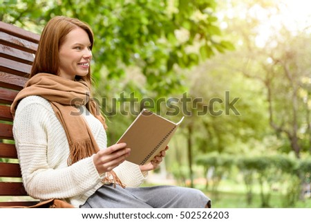 Cute young woman reading in park