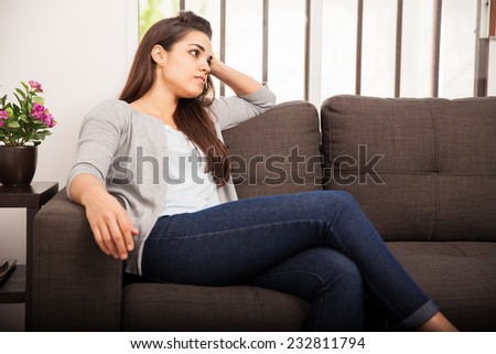 Cute young woman relaxing in a couch at home and looking away
