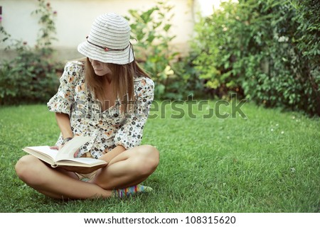 Cute young woman sitting on the grass and reading the book - stock photo