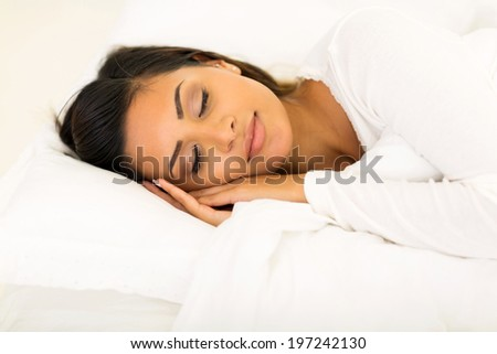 cute young woman sleeping in bed - stock photo