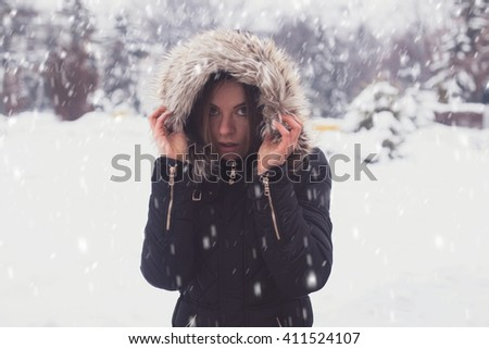 Cute young woman under showflakes in winter.