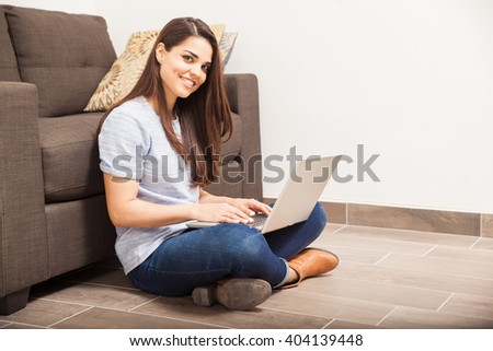 Cute young woman using a laptop computer for social media at home and smiling - stock photo