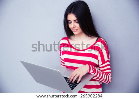 Cute young woman using laptop over gray background. Looking on the laptop - stock photo