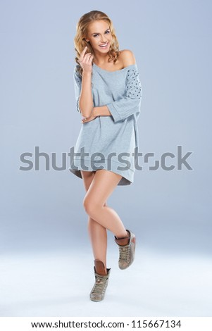 Cute young woman wearing long shirt while posing against a gray background - stock photo
