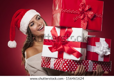 Cute young woman wearing santa hat holding christmas gifts  - stock photo