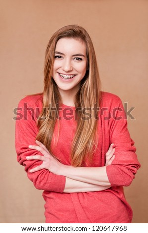 cute young woman with braces, smiling and folding her arms - stock photo