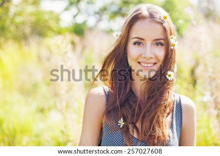 cute young woman with flowers in her hair in spring - stock photo