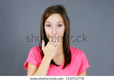 Cute young woman with hand over mouth, concept for secret, made a bad comment, oopsy, hush and others. - stock photo