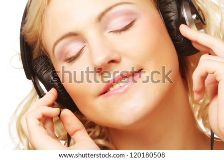 Cute young woman with headphones dancing on music with isolated background