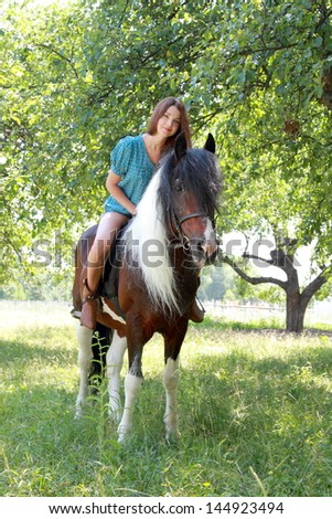 Cute young woman with long hair walking with a pony in the apple garden - stock photo