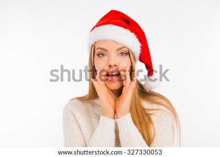 Cute young woman with santa's hat tells the news holds hand near mouth