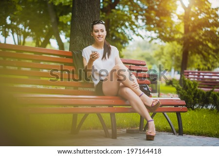 cute Young Woman with smartphone in the park - stock photo