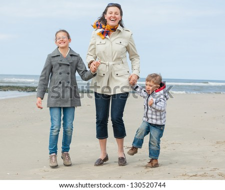 Cute young woman with two kids having fun on the Dutch beach - stock photo