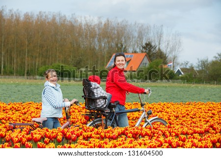 Cute young woman with two kids on bicycles in tulips fields - stock photo