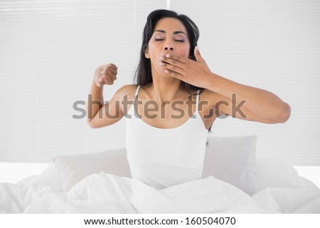 Cute young woman yawning while sitting on her bed stretching out - stock photo
