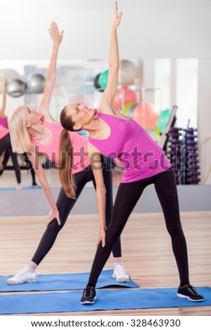 Cute young women are training their body in fitness center. They are standing and posing. The girls are stretching left arm up and looking at it. They are smiling - stock photo