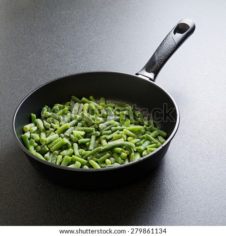 Cuted green french bean on the pan ready for frying - stock photo