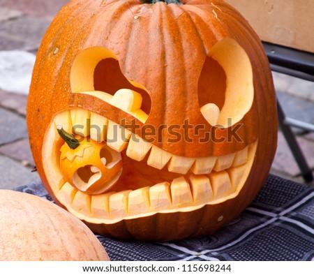 Cuted Halloween pumpkin eating small pumpkin - stock photo