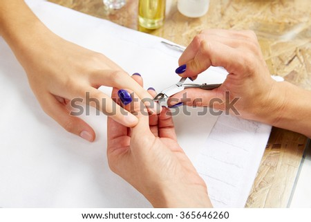 Cuticle nippers tool in nails salon woman hands treatment - stock photo