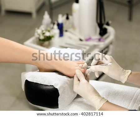 Cuticle removing in a beauty salon, on the background of the equipment