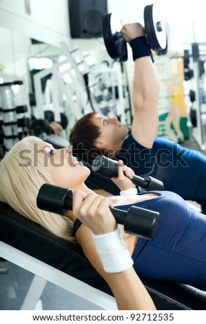 cutie athletic girl and guy,  execute exercise with dumbbells lie , in  sport-hall