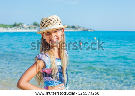 Cutie girl in hat and sun glasses on the beach - stock photo