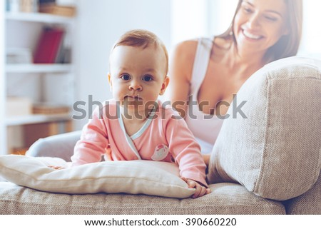 Cutie with mommy. Little baby girl looking at camera and leaning on cushion while her mother sitting on the couch at background - stock photo