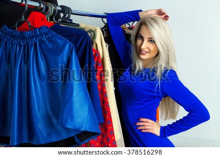 Cutie young blonde gitl in clothing store. Happy young lady with a lto of clothing. Shopping concept. - stock photo