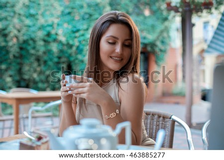 Cutie young girl with cup of tea in her hands smiling outdoors
