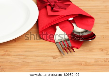 cutlery and napkin on wooden background - stock photo