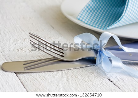 Cutlery and ribbon on old vintage wooden table closeup