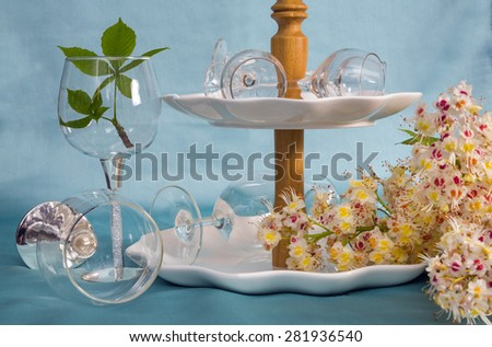 cutlery, Cake vase, wine glasses and a sprig of chestnut on a turquoise background. closeup